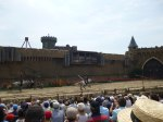 Horse riders hanging upside down as they fly past as part of the secret of the lance show at Puy du Fou
